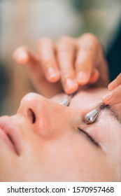 Beautiful woman receiving face massage with drainage sticks for dark circles under eyes