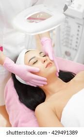 Beautiful woman receiving a facial massage in a beauty salon. The procedure of facial massage in beauty salon. Face Skin Care. Lifting Procedure. Beauty Concept. Spa Salon. Spa Face Massage.