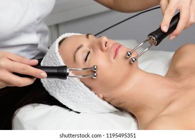 Beautiful woman receiving facial microcurrent treatment at spa salon. Beautician using electrical impulses for facial procedures.