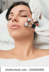 Beautiful woman receiving facial microcurrent procedure for lifting face. Facial rejuvenation and facelift with microcurrent therapy