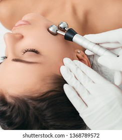 Beautiful woman receiving facial microcurrent procedure for lifting skin. Facial rejuvenation and facelift with microcurrent therapy