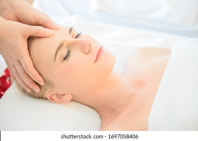 Beautiful woman receiving head and facial massage in spa salon. Concept of body health care and traditional thai massage relax