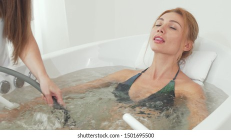 Beautiful woman receiving hydro massage in whirl pool bath. Cropped shot of a beautician doing hydro massage on a female client. Gorgeous woman enjoying relaxing hydromassage