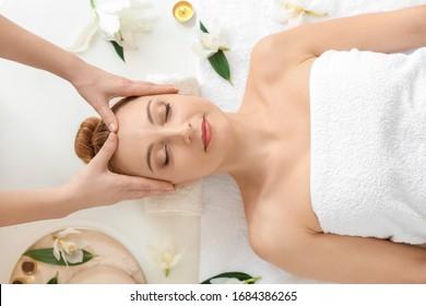 Beautiful woman receiving massage in spa salon