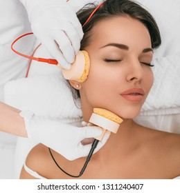 Beautiful woman receiving microcurrent procedure for facelift . Skin rejuvenation and face lift with microcurrent therapy