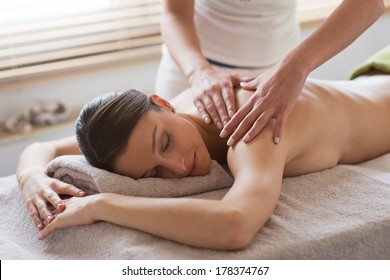 Beautiful woman receiving a relaxing back massage at spa.