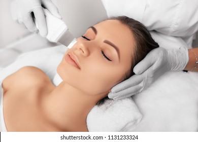 Beautiful woman receiving ultrasound cavitation facial peeling. Cosmetology and facial skin care