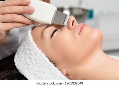 Beautiful woman receiving ultrasound cavitation facial peeling. Skin cleansing procedure at beauty spa salon.