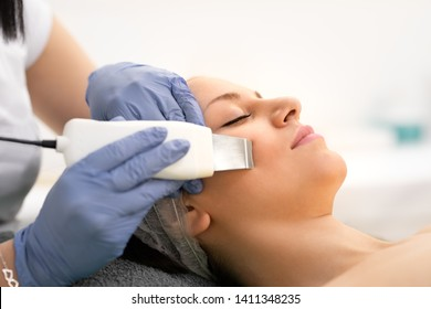 Beautiful woman receiving ultrasound cavitation facial peeling. Ultrasonic skin cleansing procedure. Beauty treatment. Beauty, spa, cosmetology and skincare concept. Cosmetologically clinic