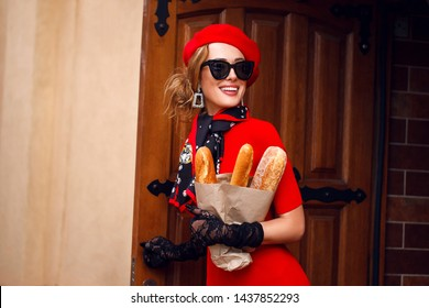 Beautiful woman in red beret and dress walks down the street of city, black gloves, dark glasses. Attractive beauty girl French style with scarf around her neck. Holding package baguette of bread