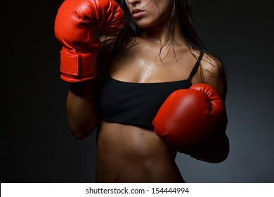 beautiful woman with the red boxing gloves, black background