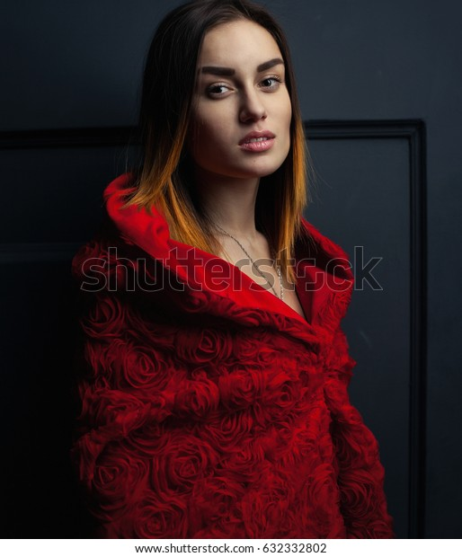 beautiful woman red cloak with red flowers roses in studio. Woman Red Riding Hood. Dramatic and fantastic shooting,fashionable toning. Like a princess
