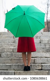 Beautiful woman in a red coat holds a green umbrella