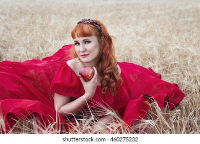 Beautiful woman in red dress with an apple in his hand sitting on a barley field.