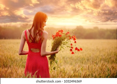 beautiful woman in a red dress with a bouquet of poppies in a wheat field at sunset, warm toning, happiness and a healthy lifestyle.