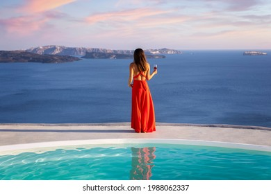 Beautiful woman in red dress  stands by the pool edge and enjoys the summer sunset with a glass of wine and view to the mediterranean sea