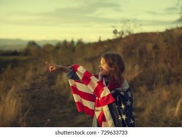 A beautiful woman in red dress walking on field with USA flag and looking on sunset