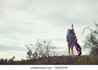 A beautiful woman in red dress walking on field with USA flag and point the hand