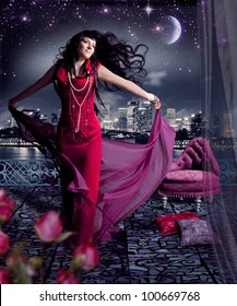 beautiful woman with red evening dress on a terrace with skyline of a city behind