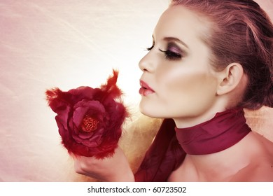 beautiful woman with red feather rose and bright make-up on pink background with copy space.