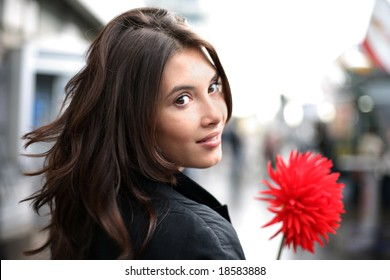 Beautiful woman with red flower walking down street, looking back. Shallow DOF.