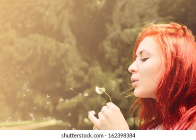 beautiful woman with red hair blows into dandelion outdoors