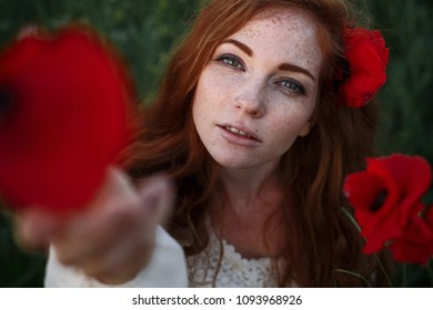 Beautiful woman with red hair and freckles in a poppy field with flowers