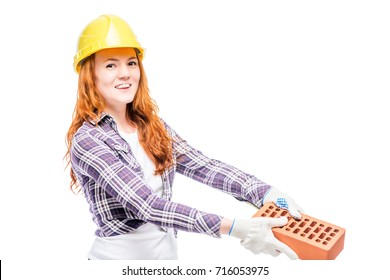 beautiful woman with red hair holds a brick, wearing a yellow helmet on her head