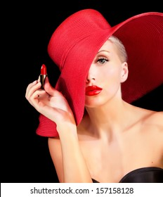 beautiful woman in red hat with red lipstick in hand