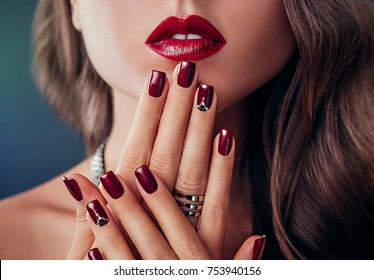 Beautiful woman with red lips and burgundy manicure