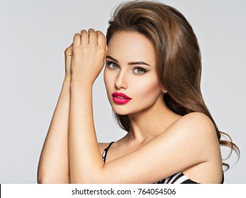 Beautiful woman with red lips. Closeup portrait with a pretty face of the young girl. Fashion model with brown hair posing at studio.