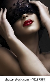 beautiful woman with red lips and lace mask over her eyes