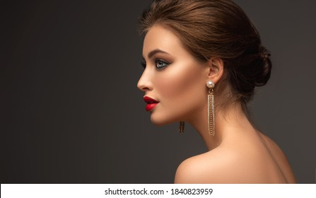 Beautiful woman with red lipstick on her lips and long earrings. Beauty girl with elegant hairstyle and evening make-up. Makeup, cosmetics and jewelry