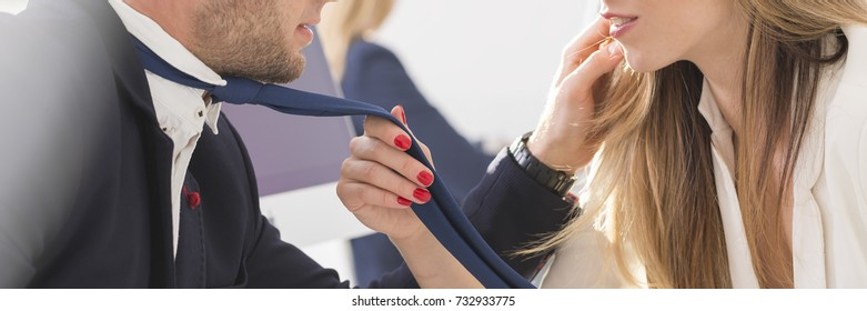 Beautiful woman with red nails touching blue tie of a handsome man