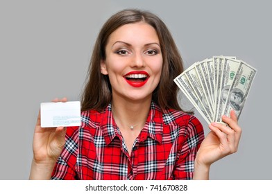 Beautiful woman in a red plaid shirt and enjoys a large amount of money in her hand and a credit card