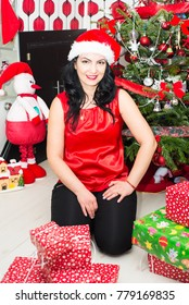 Beautiful woman in red posing home in front of Christmas tree woth presents