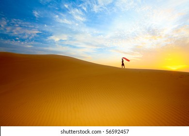 Beautiful woman with red shawl in desert