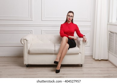 Beautiful woman in red shirt and eyeglasses sitting on a sofa