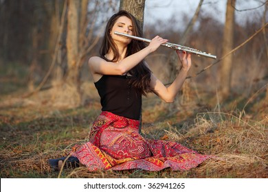 A beautiful woman in red skirt posing in a forest while playing on a flute.