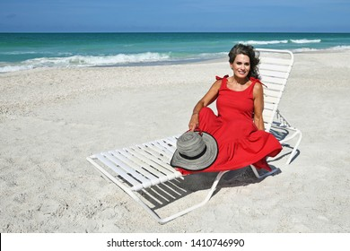 Beautiful Woman in a Red Summer Dress and Hat Sitting on the Beach