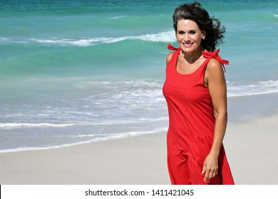 Beautiful Woman in a Red Summer Dress Standing on the Beach