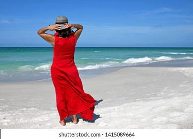 Beautiful Woman in a Red Summer Dress Standing on the Beach Holding Her Hat on her Head to keep it from Blowing Away.