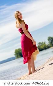 Beautiful woman with a red sun-dress walking along the beach