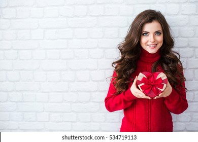 Beautiful woman in a red sweater with a Christmas present form of heart on background white brick wall with copy space.