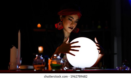A beautiful woman with a red turban and red earring act as a fortune teller in a dark room. She is spreading her fingers to touch a white shining ball and seriously look at it.
