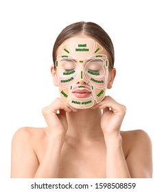 Beautiful woman with reflexology massage chart on her face against white background