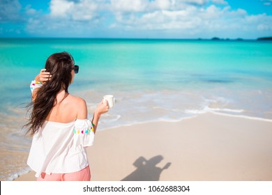 Beautiful woman relax during exotic vacation on the beach enjoying sweet coffee