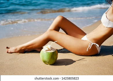 Beautiful woman relax on tropical sandy beach with coconut. Vacation concept, summer background