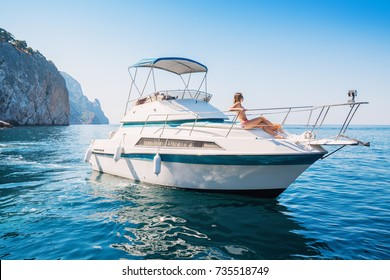 Beautiful woman relaxes on a private yacht in the sea near the islands.