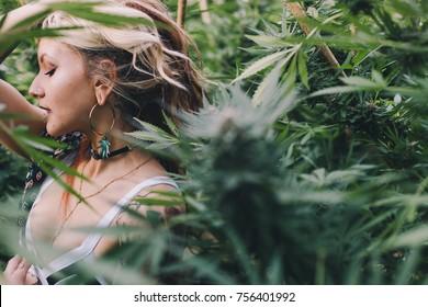 Beautiful woman relaxing in a cannabis garden